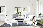 Sheepskins on white garden chairs, pale grey couch and designer standard lamp in lounge area