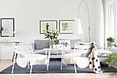 weiße Gartenstühle mit Tierfell, hellgraue Polstercouch und Designer-Stehleuchte im Loungebereich