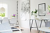 Delicate glass-topped console table next to large artwork in bright dining area