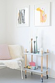 Pastel candlesticks on top of serving trolley next to animal-skin blanket on bench