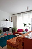 White furniture and colourful home textiles in small living room