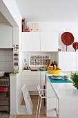 Offene Küche mit Theke und einzelnen weißen Elementen