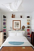 Bookcases around bed headboard in small bedroom