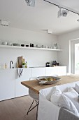weiße Einbauküche mit offenem Regal und langem Esstisch aus Holz