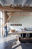 Rustikaler Esstisch und Designerstühle in umgebauter Scheune, Frau am Fenster