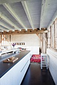Elegante Kücheninsel in umgebauter Scheune mit rustikaler Holzbalkendecke