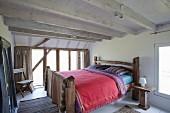 Rustikales Doppelbett aus Holz in Schlafraum weisser Holzbalkendecke