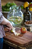 Apfel auf rustikalem Holzbrett schneiden
