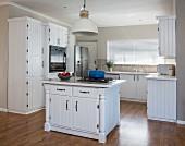Landhausküche mit weißen Bretter-Fronten und Kochinsel
