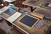 Slates, pencil boxes and hand-sewn wiping cloth on vintage school desk