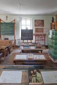 Blackboards, vintage school desks and open schoolbooks in classroom in school museum