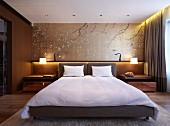 Elegantes Schlafzimmer mit Doppelbett und Polsterkopfteil, dahinter Wandgestaltung mit dekorativen, asiatischen Ästemotiven