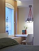 Desk in niche below pendant lamp in corner of bedroom