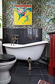 Free-standing clawfoot bathtub, black splashback on wall and modern artwork on floral wallpaper in vintage-style bathroom