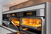 An illuminated oven and a combi-steamer with an open door at eye level