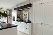 An open-plan kitchen with a white, built-in cupboard next to a work surface in a niche with an integrated extractor fan