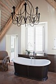 Free-standing bathtub and chandelier in attic bathroom