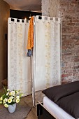 Fabric screen brightened up with vintage floral patterns in front of brick wall in bedroom