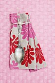 Vintage spoon on floral linen napkin on pink place mat