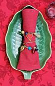 Perlenschmuck um rote Stoffserviette gewickelt auf grüner Schale in Blattform, rote Tischdecke mit Muster