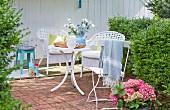 Terrassenplatz mit weissen Korbstühlen, Klappstuhl und Tisch in sommerlichem Garten