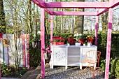 Pinkfarbene Pergola und eine Anrichte im Garten