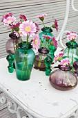 Pink gerbera daisies in various glass vases on metal chair