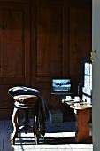Rustikale Holzbank als Ablagefläche mit Kaffeetassen und Laptop vor holzverkleideter Wand, im Vordergrund Holzhocker