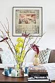 Glasvase mit Blüten, Kerzen und Bücherstapel vor gerahmtem Zeitungsausschnitt und Couch
