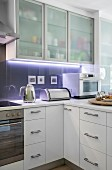 Translucent cupboards and indirect lighting in modern kitchen