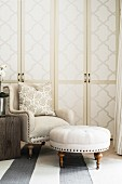 Armchair and footstool in front of cupboards with wallpapered doors
