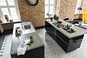 Kitchen islands with polished concrete work surfaces over black cupboards with cement floor tiles in a retro pattern