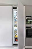 A built-in, floor-to-ceiling cupboard with an open fridge door