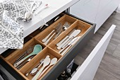 An open drawer with a wooden cutlery holder