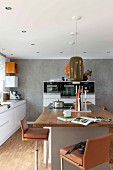 Bar stools with brown leather covers around a kitchen island with a pendant lamp with a retro ceramic shade in a modern kitchen