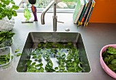 A stainless steel work surface with an integrated sink and washed salad