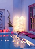 Lit floating candles in pool with purple cushions on side and stacked illuminated paper lanterns in corner