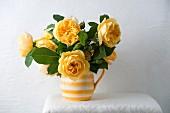 Rosenstrauss aus gelben Rosen in gelb-weiss getreiftem Krug