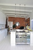 Open-plan kitchen with white floor and brick wall
