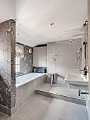 Elegant bathroom in shades of grey with floral wallpaper around bathtub area