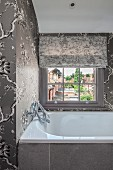 Elegant bathroom in shades of grey with floral wallpaper and lattice window