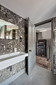 Elegant bathroom with floral wallpaper and view of hallway