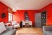 Desk and armchairs against red walls in renovated period apartment