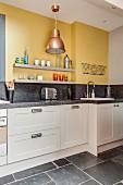 Küchenzeile mit Granit-Arbeitsplatte und zwei graue Wandboards an gelber Wand