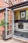 Geöffnete Terrassenfenstertür in traditionellem Ziegelbau mit Blick auf Küchenzeile