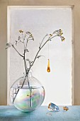 Glass ornament hanging from flowering branch in spherical glass vase