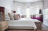 Bed with button-tufted headboard and sides in elegant bedroom