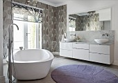 Free-standing bathtub and patterned wallpaper in elegant bathroom