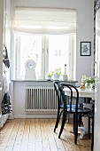 Black chairs at round white table in front of kitchen window