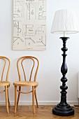 Alte Illustration hängt über Thonetstühlen und Stehleuchte